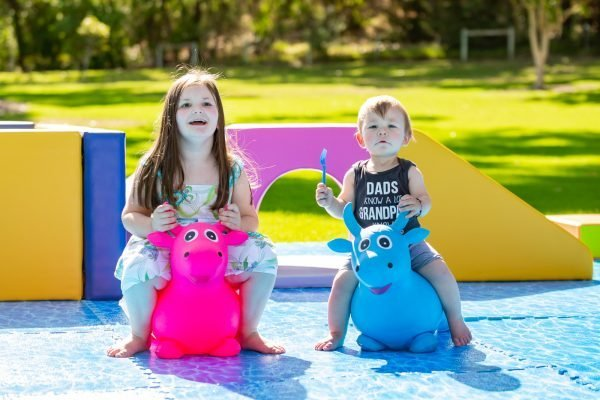 This is an image of two small children riding the Bouncy Buddies soft cows
